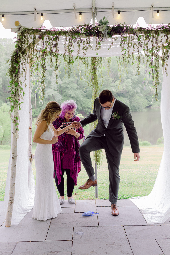 A groom holds hands with a bride while stepping on a glass in a Jewish wedding ceremony at Mountain Lakes House in Princeton NJ by Laura Billingham