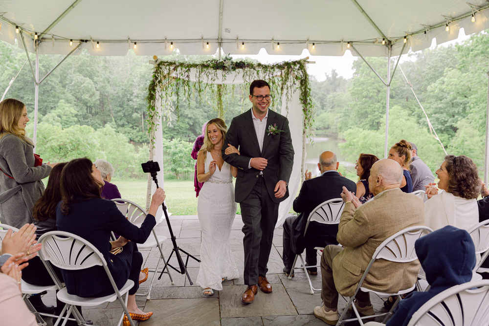 Bride and groom walk away from their wedding ceremony at Mountain Lakes House in Princeton NJ by Laura Billingham Photography