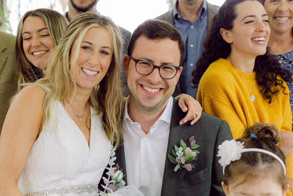 A bride and groom smile surrounded by family at Mountain Lakes House in Princeton NJ by Laura Billingham Photography
