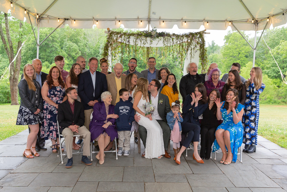 A bride and groom smile at each other surrounded by family at Mountain Lakes House in Princeton NJ by Laura Billingham Photography