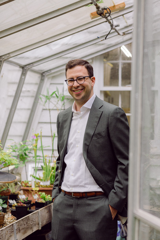 Portrait of a smiling groom in the green house at Mountain Lakes House in Princeton NJ by Laura Billingham Photography