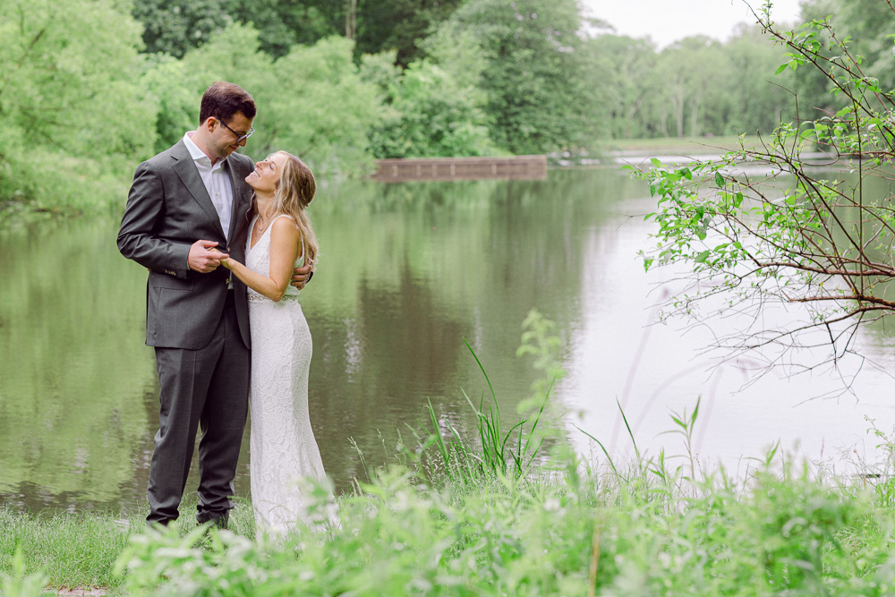 An elegant bride and groom embrace near the lake at Mountain Lakes House in Princeton NJ by Laura Billingham Photography