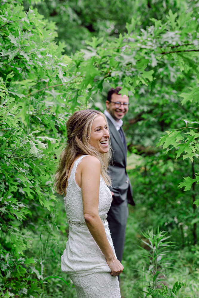 A bride and groom walk through the woods at Mountain Lakes House in Princeton NJ by Laura Billingham Photography