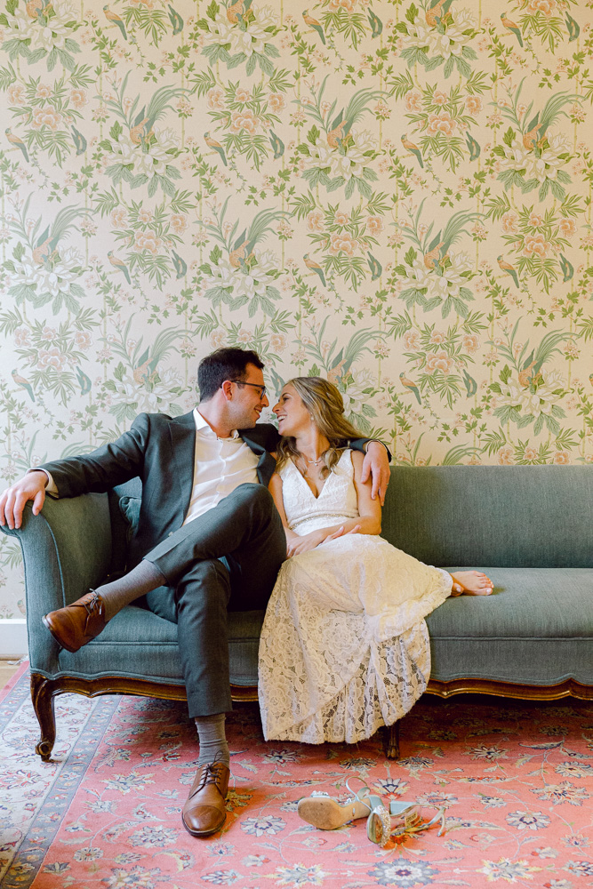 Elegant bride and groom snuggle on a couch at Mountain Lakes House in Princeton, NJ by Laura Billingham Photography