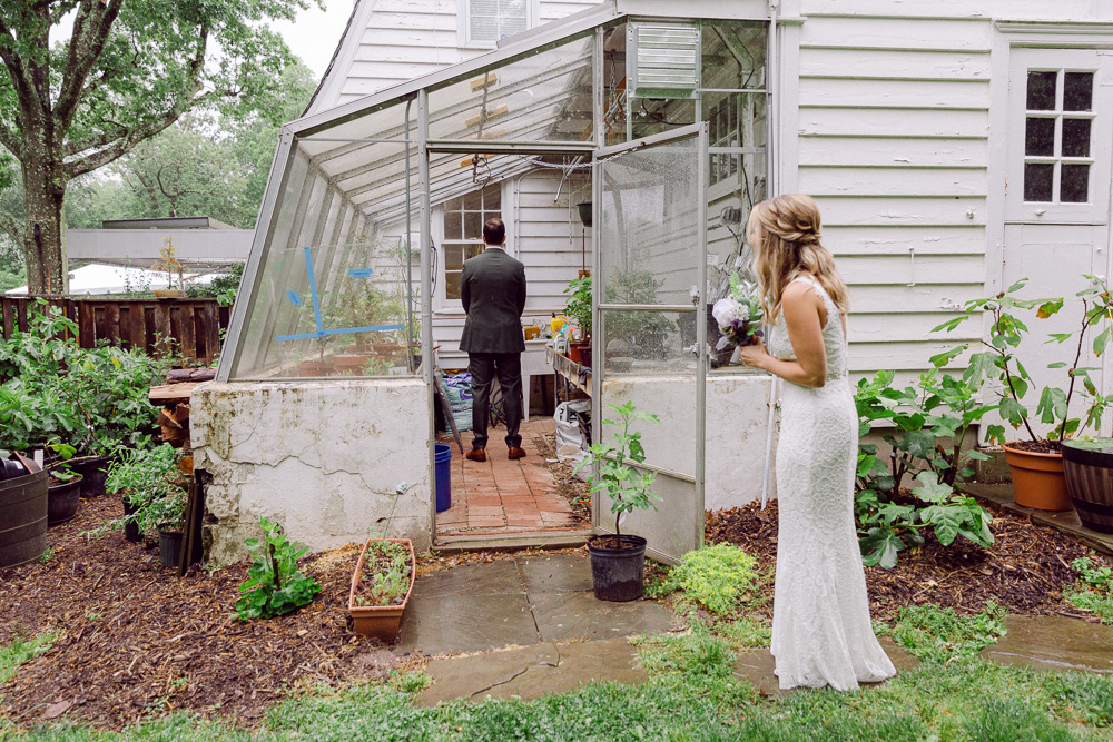 bride walks toward the groom in the greenhouse at Mountain Lakes House by Laura Billingham Photography