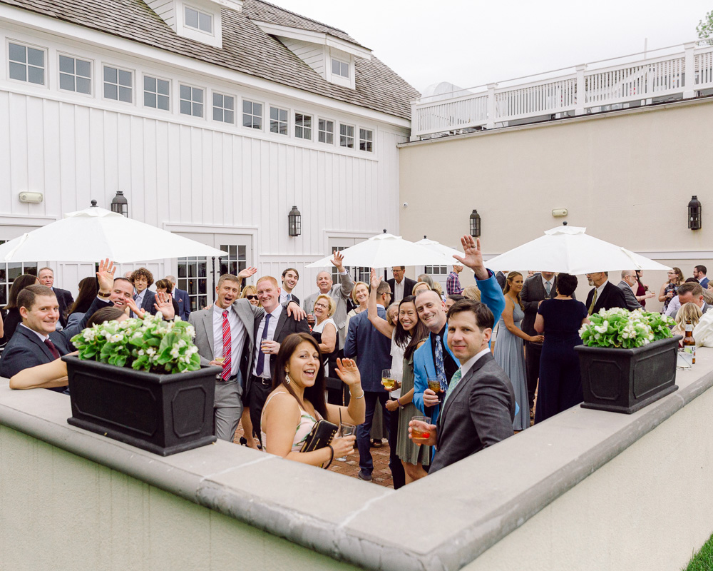 a lively crowd of wedding guests waves during a cocktail hour at the Ryland Inn Coach House in Whitehouse Station, NJ by Laura Billingham Photography