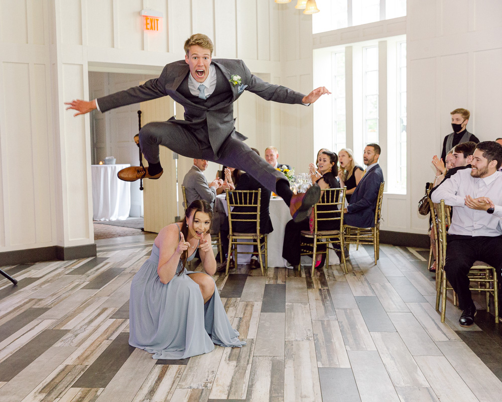 brother of the groom hurdles over a bridesmaid during an entrance to a wedding reception at the Ryland Inn in Whitehouse Station, NJ by Laura Billingham Photography
