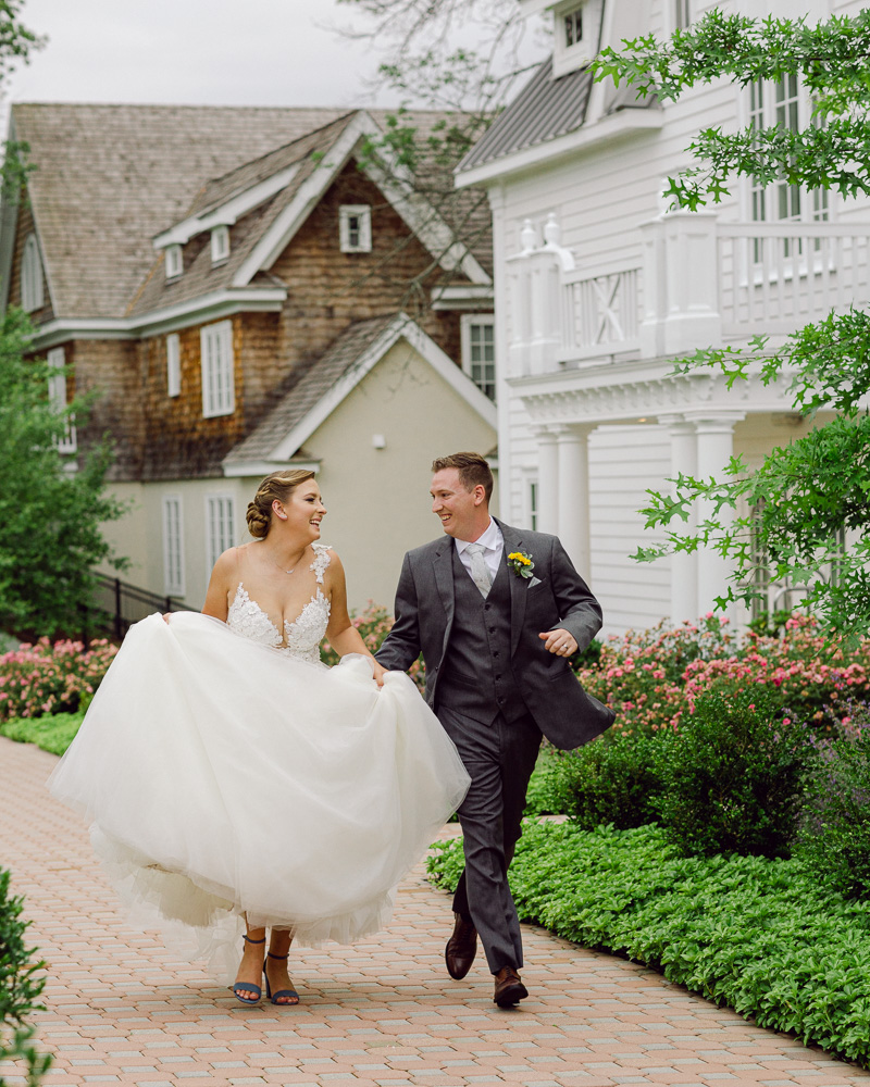 Energetic bride and groom in elegant attire run and laugh at the Coach House at the Ryland Inn in Whitehouse Station, NJ by Laura Billingham Photography