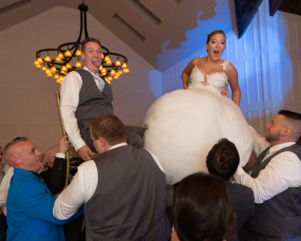 Jubilant bride and groom are lifted on chairs at their wedding reception in the Coach House at the Ryland Inn in Whitehouse Station, NJ by Laura Billingham Photography