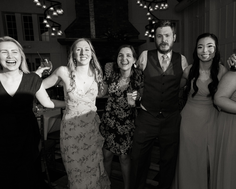 black and white photo of wedding reception guests dancing arm in arm at the Coach House at the Ryland Inn by Laura Billingham Photography