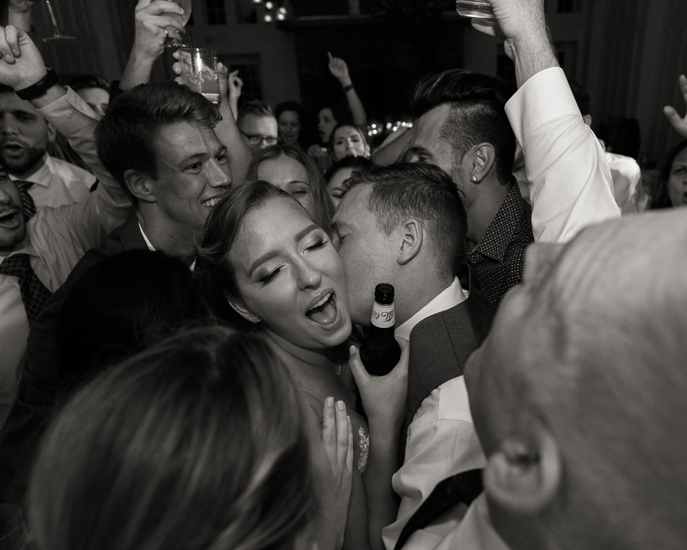 black and white photo of bride and groom embrace by their friends at their wedding reception at the Coach House at the Ryland Inn by Laura Billingham Photography