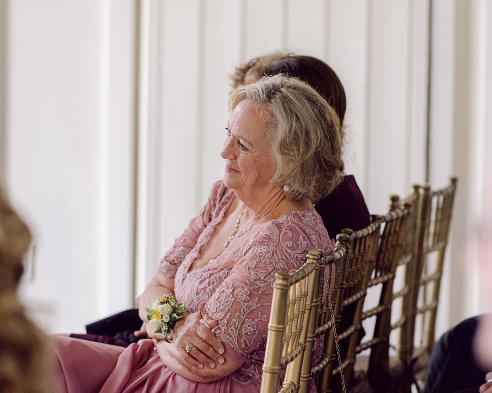 Mother of the groom watches elegant wedding ceremony in the Coach House at the Ryland Inn in Whitehouse Station, NJ by Laura Billingham Photography