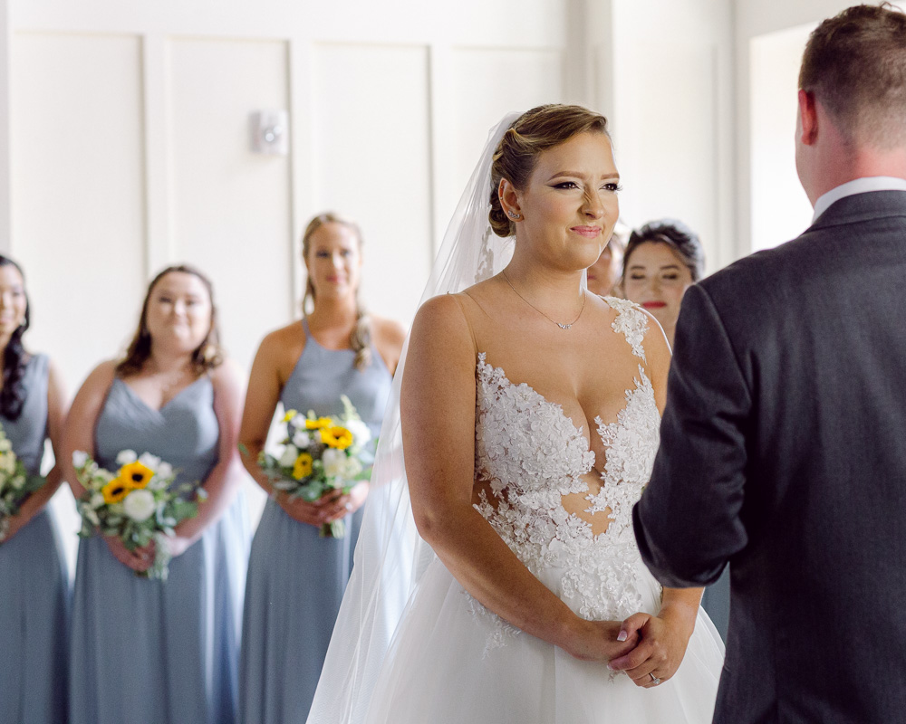 Elegant bride makes a funny face at the groom during their wedding ceremony in the Coach House at the Ryland Inn in Whitehouse Station, NJ by Laura Billingham Photography
