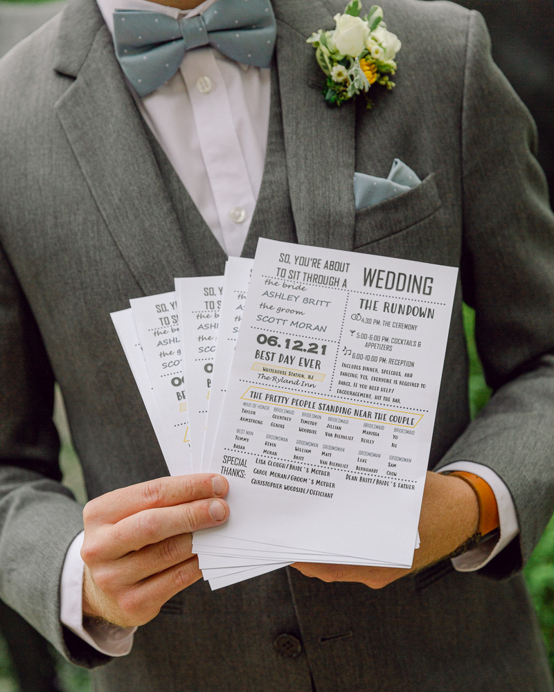 Bridal attendant holds ceremony programs for a summer wedding at the Ryland Inn in Whitehouse Station, NJ by Laura Billingham Photography