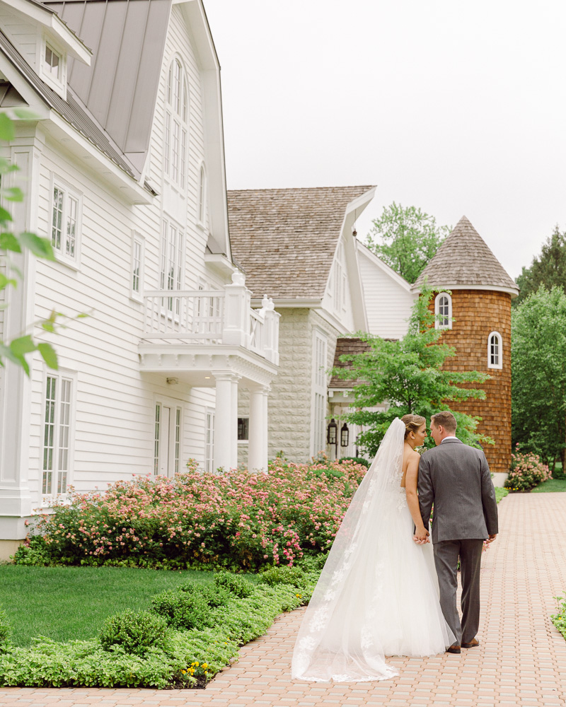 Elegant bride and groom walk hand in hand in front of the Coach House at the Ryland Inn in Whitehouse Station, NJ by Laura Billingham Photography