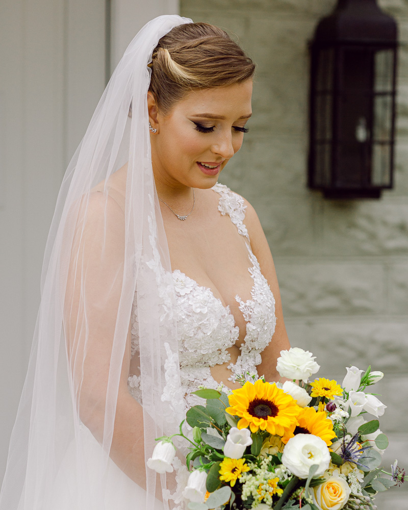 Elegant bride with long veil holds a bouquet of sunflowers