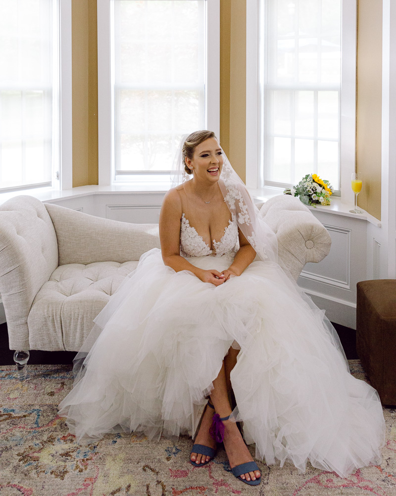 Happy bride in an elegant gown smiles inside the bridal suite at the Ryland Inn in Whitehouse Station, NJ by Laura Billingham Photography