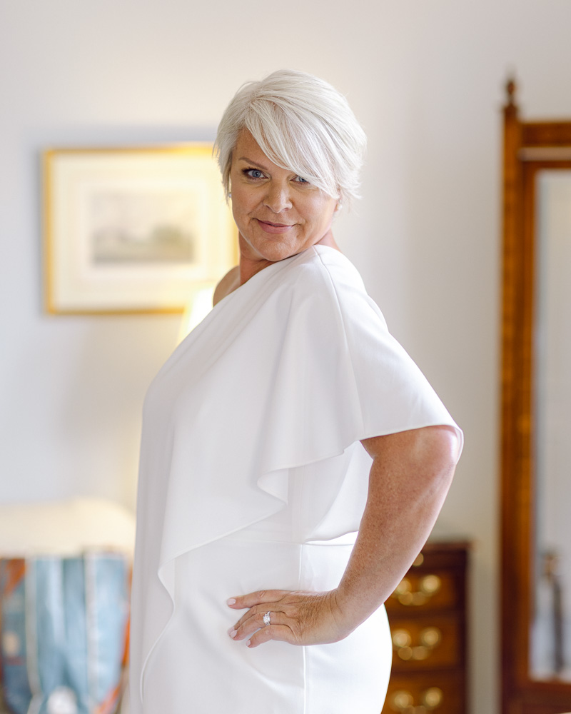Stylish and elegant bride with white hair confidently poses in the bridal suite at the Bernards Inn in Bernardsville, NJ