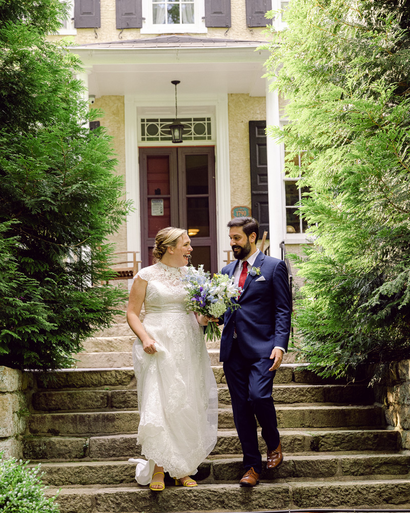 Elegant bride and groom descend stairs in front of HollyHedge Estate in New Hope, PA