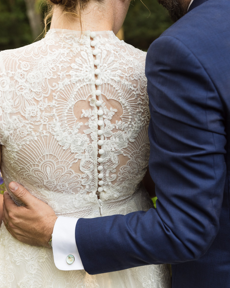 detail of the lace back of bride's elegant gown and groom embracing her at HollyHedge Estate in New Hope, PA