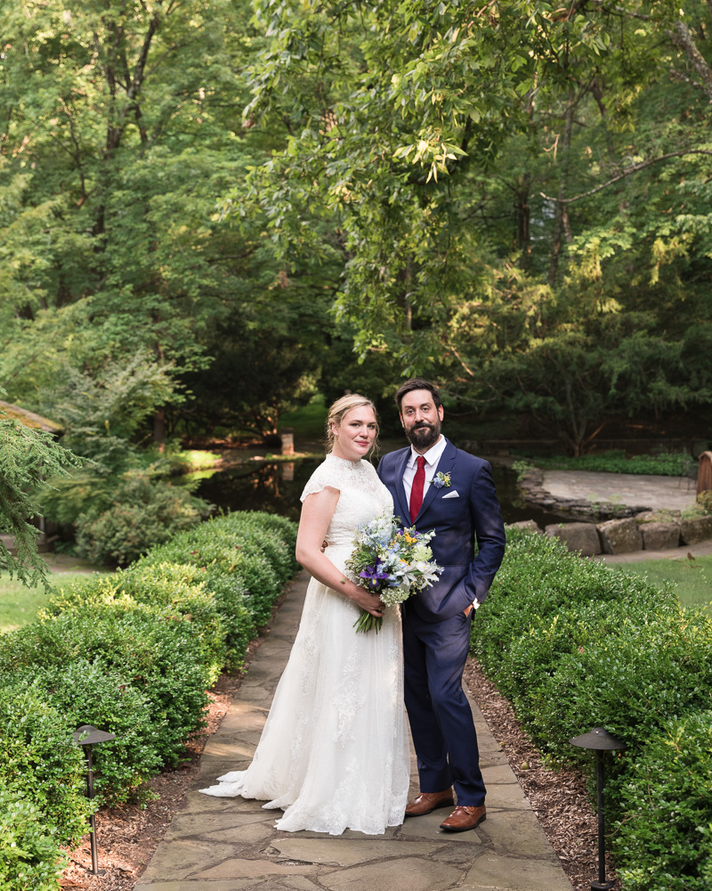 Elegant bride and groom pose in front of pond at HollyHedge Estate in New Hope, PA
