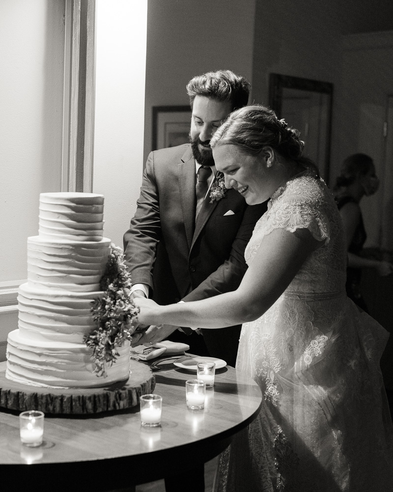 black and white photo of elegant bride and groom cutting their wedding cake at HollyHedge Estate in New Hope, PA