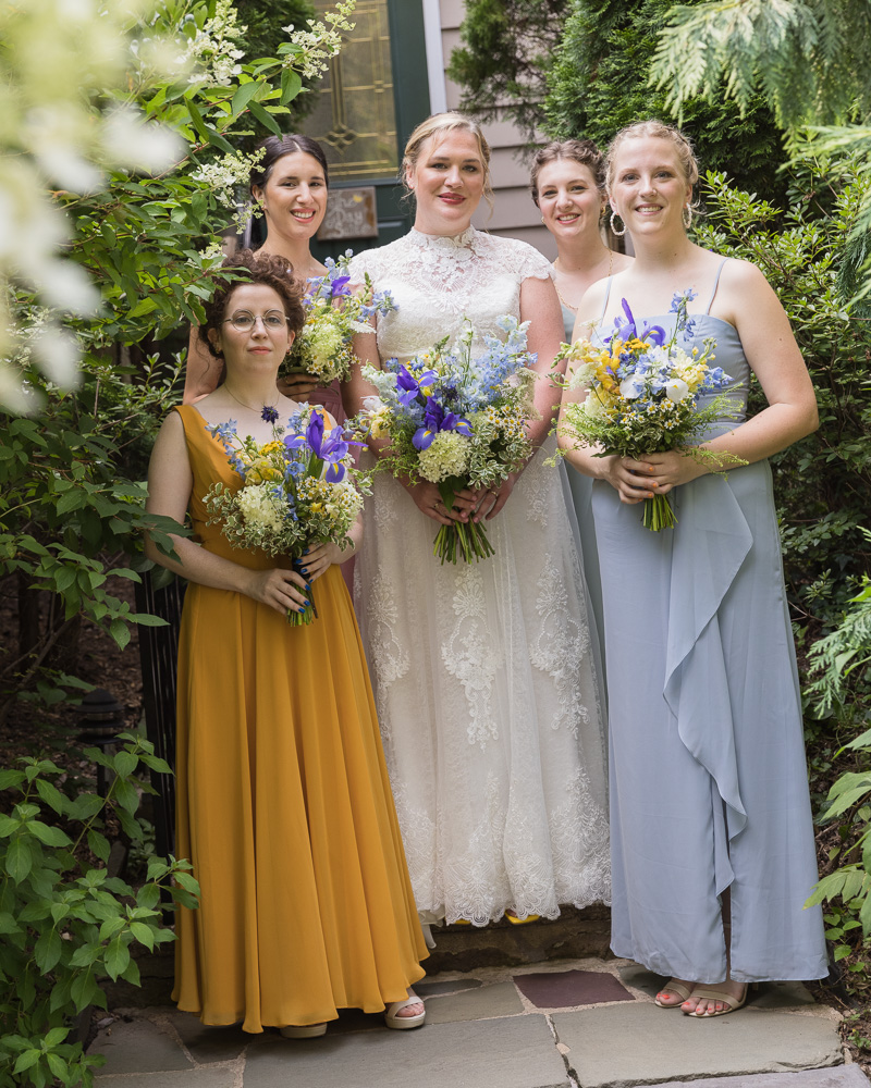 bride with bridesmaids in different pastel gowns at Hedge Estate by Laura Billingham Photography